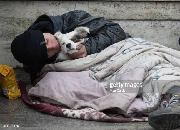 A homeless man sits with his dog in central Bucharest on February 7 2017 in Bucharest Romania Romania's ruling Social Democrats has appealed for calm...
