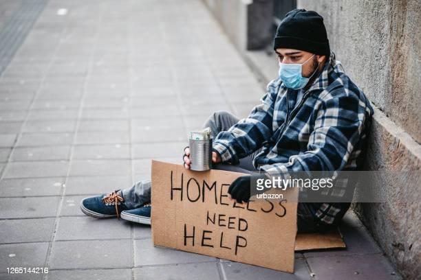 hombre sin hogar sentado y pidiendo ayuda - sin techo fotografías e imágenes de stock