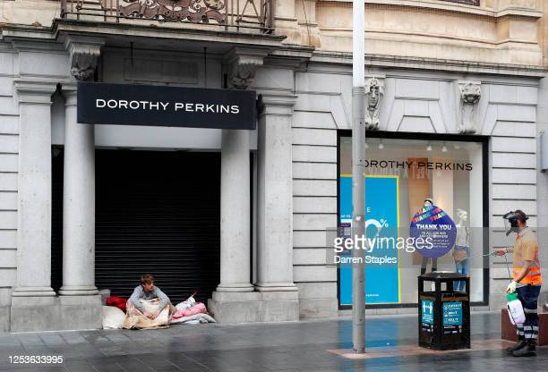 Homeless man sitting in the doorway of a closed Dorothy Perkins clothes store watches a council worker clean street furniture during lockdown on July...