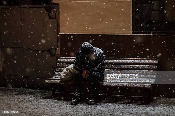 homeless man sitting on bench in blizzard - homeless foto e immagini stock