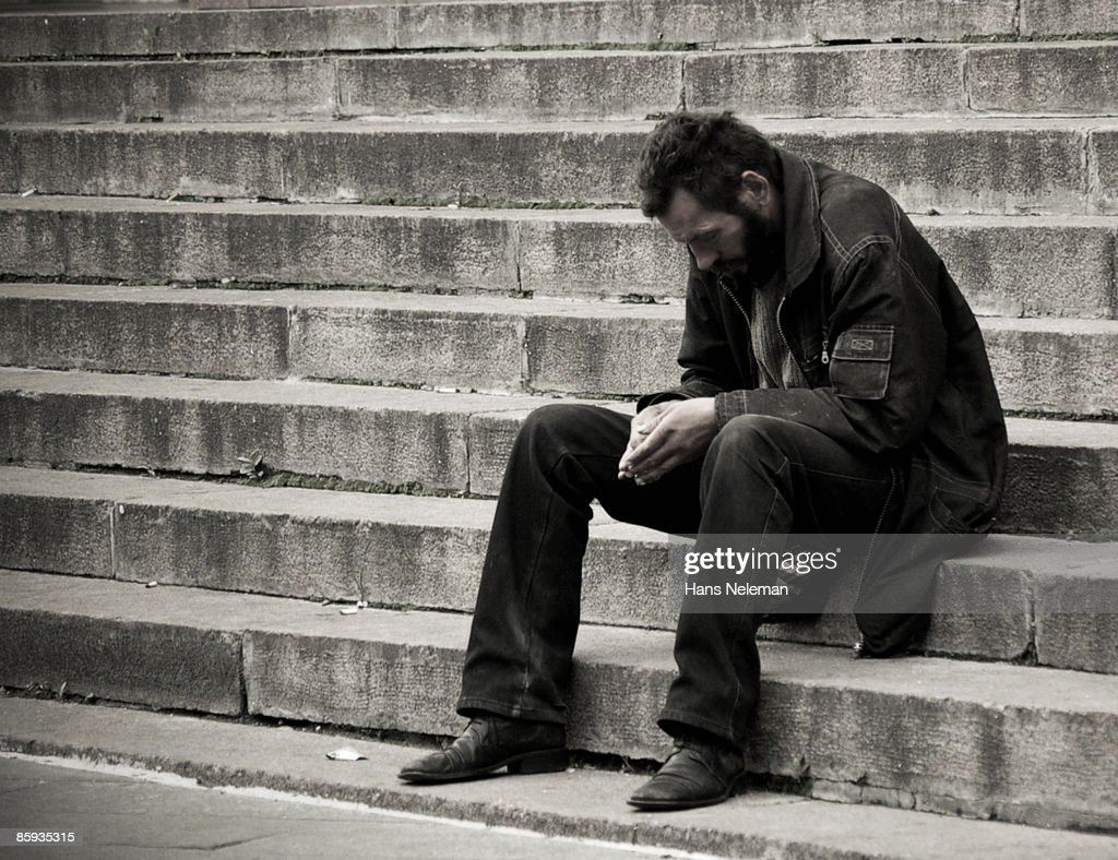 Homeless man sitting on steps in Kiev, Ukraine : Stock Photo