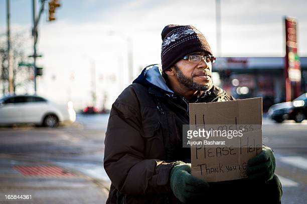 Homeless man sitting right on the edge of the street asking cars passing by to help out