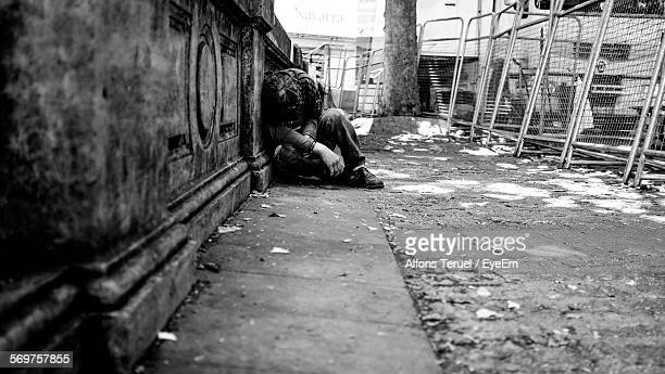 Homeless Man Sleeping By Retaining Wall