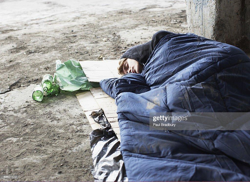 Homeless man sleeping in sleeping bag on cardboard : Stock Photo