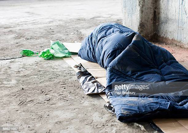 homeless man sleeping in sleeping bag on cardboard - homeless stock photos and pictures