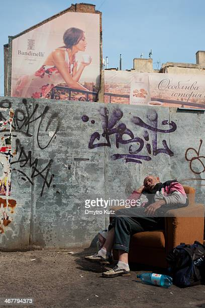 Homeless man sleeping in the arm-chair in the street, with the huge mural commercial portraying beautiful woman on the balcony with a cup of coffee...