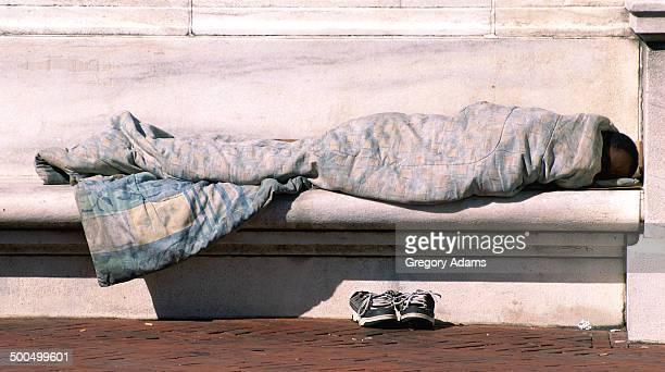 Homeless man sleeping on a stone bench near the capital building in Washington D.C., USA