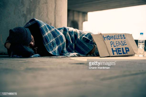 homeless man sleeping on cardboard - homelessness stock pictures, royalty-free photos & images