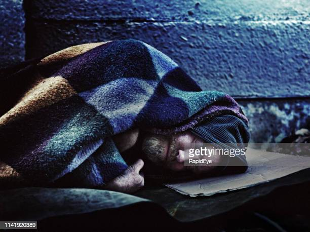 homeless man sleeping on sidewalk - homeless foto e immagini stock