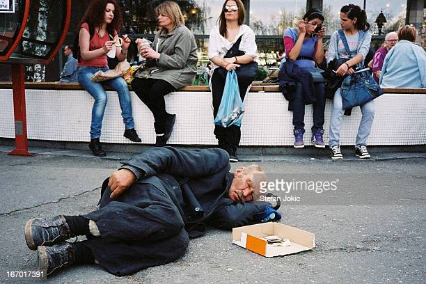 Homeless man sleeping on the street in front of fountain. Trg Republike, Belgrade, Serbia, 2012