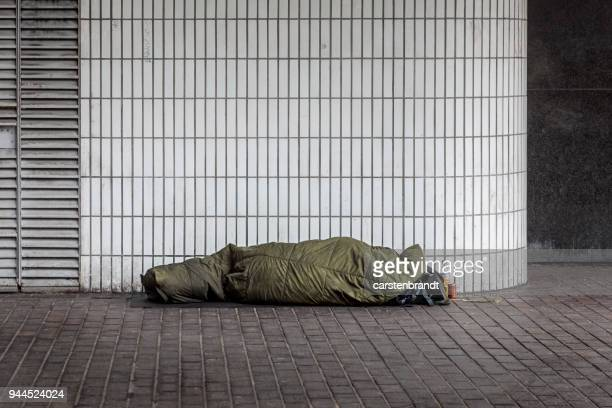 homeless man sleeping outside euston station - homeless foto e immagini stock