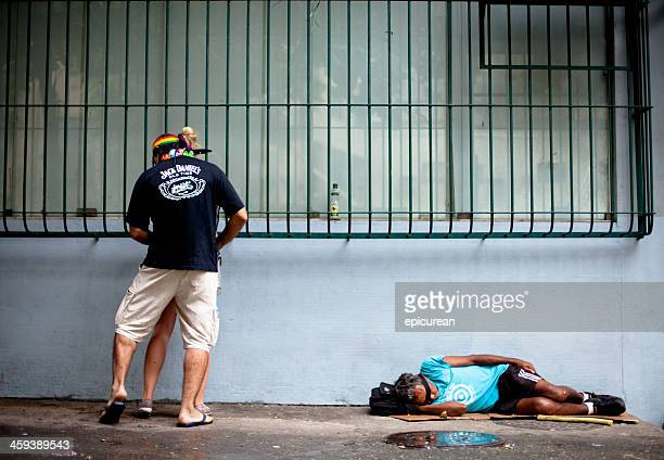 Homeless man sleeping while drunk couple makes out above him