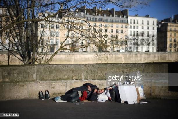 A homeless man sleeps along the river Seine in front of the SaintLouis island in Paris on December 28 2017 / AFP PHOTO / Eric FEFERBERG