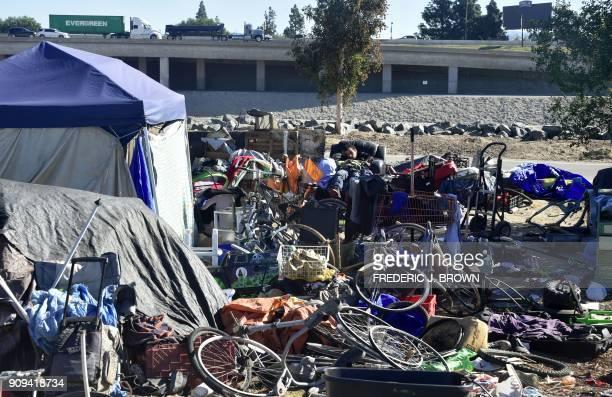 A homeless man sleeps at a homeless encampment along the Santa Ana River beside Angel Stadium in Anaheim California on January 23 2018 January 22...