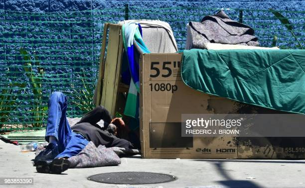 A homeless man sleeps beside his makeshift temporary shelter on a street in downtown Los Angeles California on June 25 as a United Nations report on...