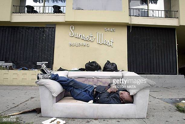 A homeless man sleeps in a couch on the sidewalk of Sunset Boulevard in Hollywood 11 June 2003 A recent survey by the United States Department of...