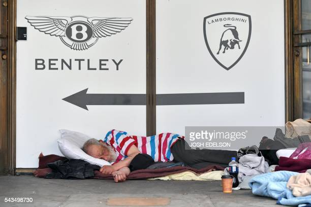 A homeless man sleeps in front of a luxury auto dealership in San Francisco California on June 2016 Homelessness is on the rise in the city irking...