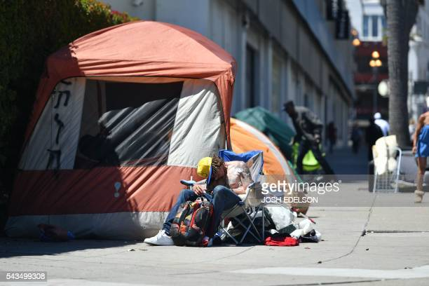A homeless man sleeps in front of his tent along Van Ness Avenue in downtown San Francisco California on June 2016 Homelessness is on the rise in the...