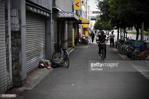 A homeless man sleeps in the street near the slum area of Kamagasaki on April 24 2016 in Osaka Japan Kamagasaki a district in Japan's second largest...