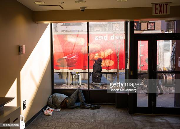 A homeless man sleeps inside a Chase Bank ATM room during a cold weather period February 24 2015 in the Brooklyn borough of New York