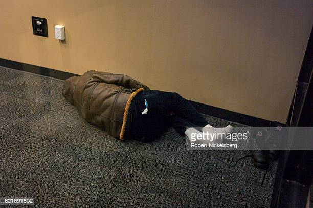 A homeless man sleeps inside an ATM room of the Chase Bank in Brooklyn New York October 29 2016
