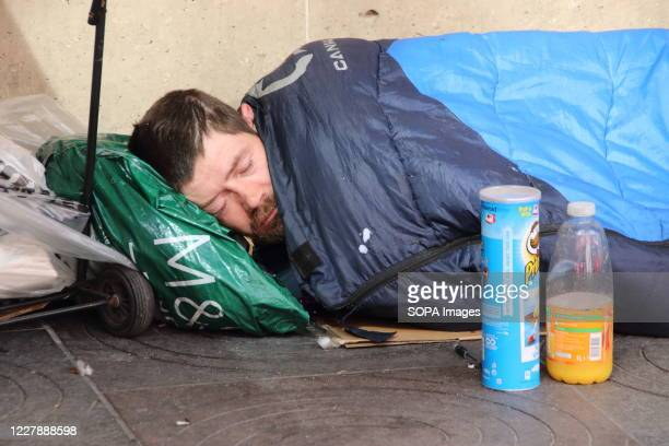 A homeless man sleeps near Green Park tube station with an orange drink and tube of Pringles crisps near him London has seen a surge in rough...