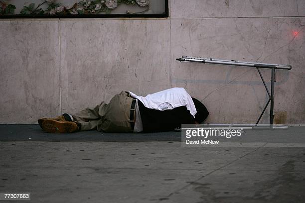 A homeless man sleeps next to a walker on a sidewalk where people wake up before dawn to dismantle their beds and encampments before businesses open...