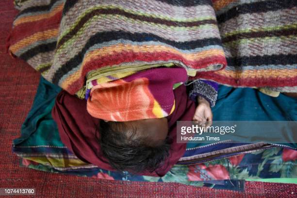 A homeless man sleeps next to his child inside a shelter home at Nizamuddin Basti on December 18 2018 in New Delhi India There are some 83 permanent...