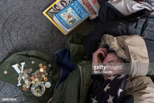 A homeless man sleeps next to monetary donations from the public and his books outside Green Park underground station on December 16 2017 in London...