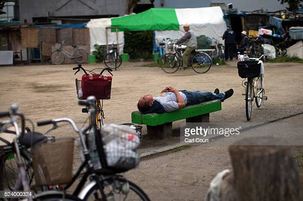 A homeless man sleeps on a bench in the slum area of Kamagasaki on April 23 2016 in Osaka Japan Kamagasaki a district in Japan's second largest city...