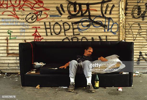 A homeless man sleeps on a discarded couch in the East Village