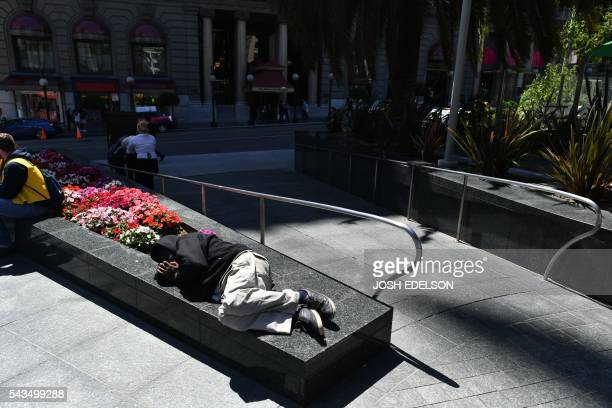 A homeless man sleeps on a planter in San Francisco California on Tuesday June 2016 Homelessness is on the rise in the city irking residents and...