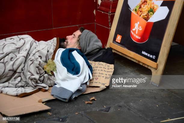 A homeless man sleeps on a sidewalk in London England