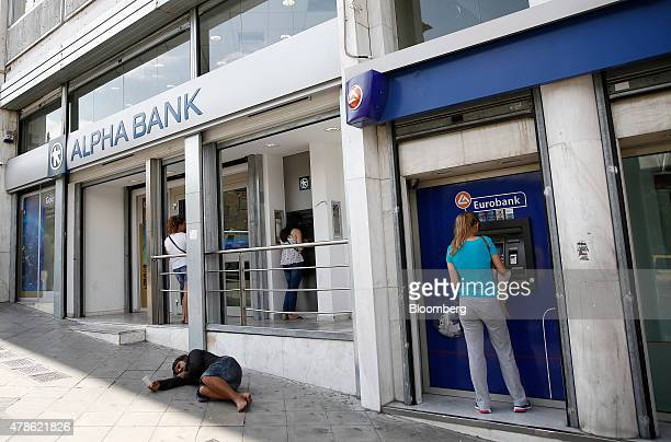 A homeless man sleeps on the floor as customers use automated teller machines outside a Eurobank Ergasias SA bank branch and an Alpha Bank AE branch...
