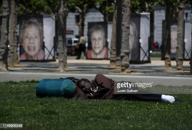 A homeless man sleeps on the grass at Civic Center Plaza on May 17 2019 in San Francisco California Results of a twoyear Homelessness PointinTime...
