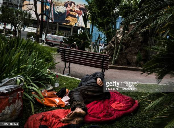 A homeless man sleeps on the lawn of a public square opposite the festival's palace on which is displayed the official poster of the 71th Cannes Film...