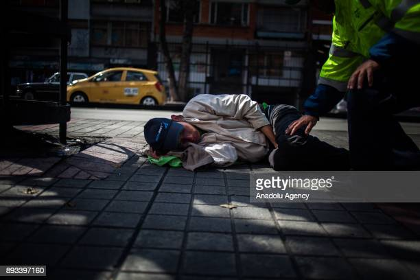 A homeless man sleeps on the pavement in Bogota Colombia on December 15 2017 Homeless people who are called 'CHC' Ciudadanos Habitantes de la Calle...