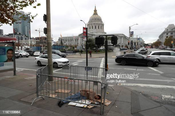 A homeless man sleeps on the sidewalk near San Francisco City Hall on December 05 2019 in San Francisco California California Gov Gavin Newsom...