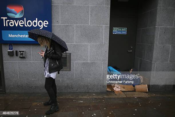 A homeless man sleeps rough in the doorway of a hotel on the streets of Manchester on February 26 2015 in Manchester United Kingdom As the United...
