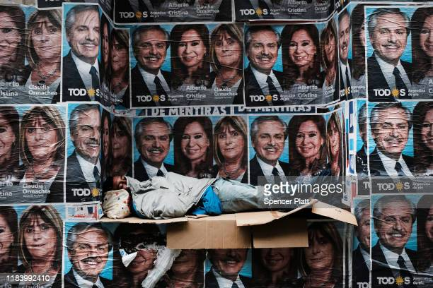 A homeless man sleeps under posters of newly elected president Alberto Fernandez and his running mate Cristina Fernández de Kirchner as people walk...