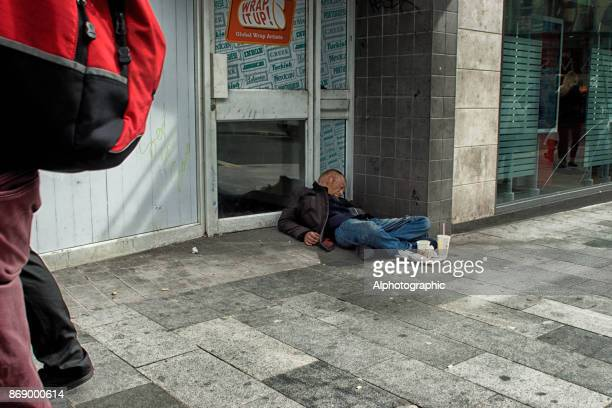 A homeless man slouched against a doorway