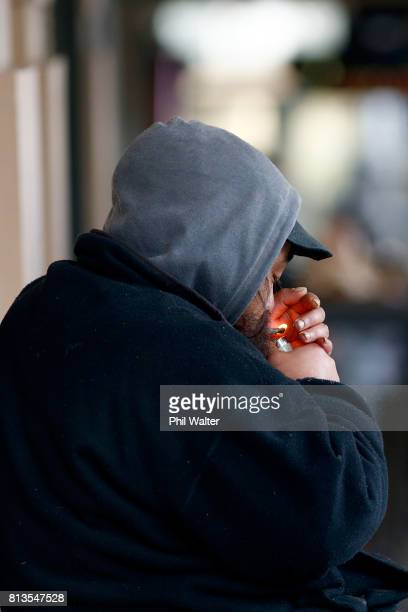 A homeless man smokes as he sits on the street in the Auckland CBD on July 13 2017 in Auckland New Zealand Research by Roy Morgan found that economic...