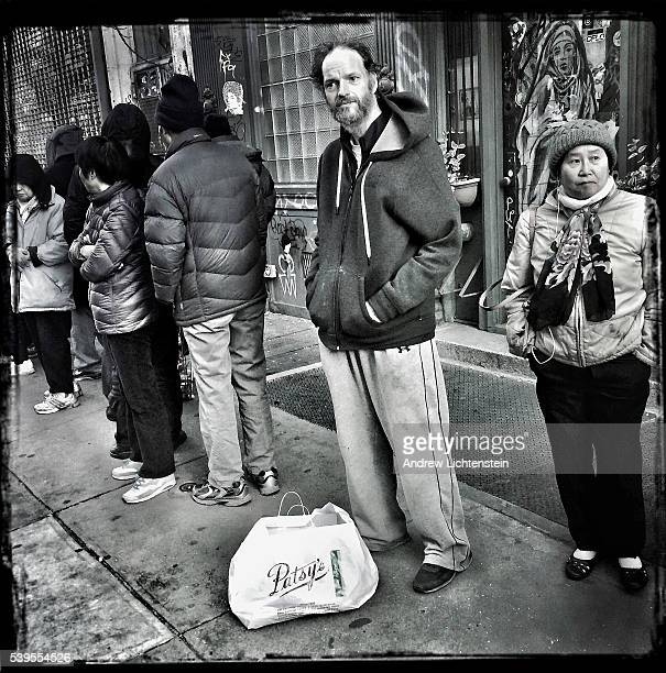 A homeless man stands in line for a Thanksgiving meal outside of the Bowery Mission