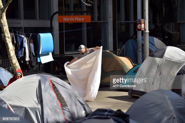 A homeless man takes care of his laundry among tents at Martin Place in the central business district of Sydney on August 10 2017 The New South Wales...