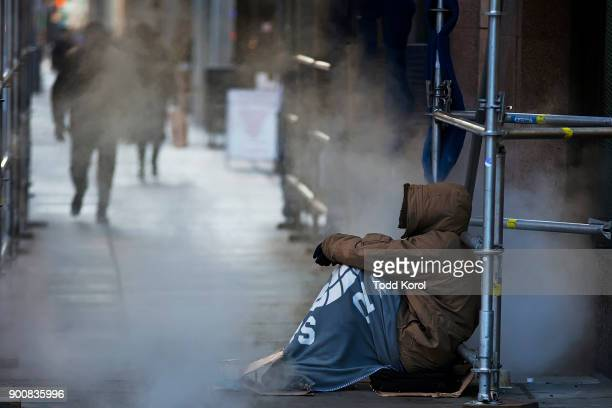 A homeless man tries to keep warm near a steam vent in the bone chilling winter temperatures of 13 in downtown Toronto Ontario