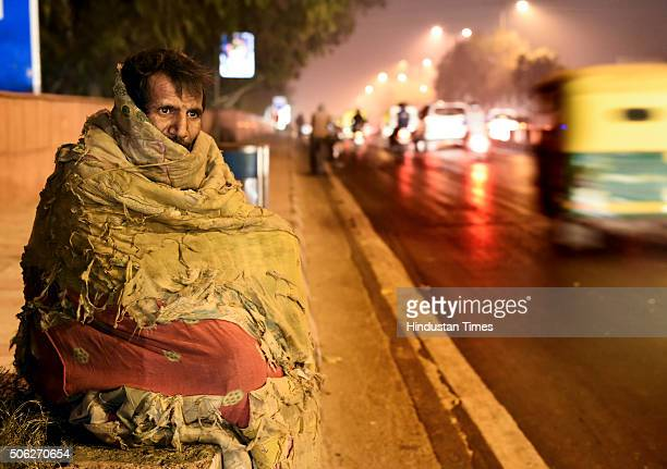 A homeless man tries to stay warm in a blanket on cold winter morning at ITO Road on January 22 2016 in New Delhi India Delhi today recorded the...