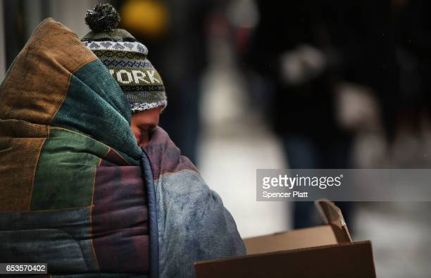 A homeless man tries to stay warm on a Manhattan street on an unseasonably cold day on March 15 2017 in New York City New Yorkers are getting back to...
