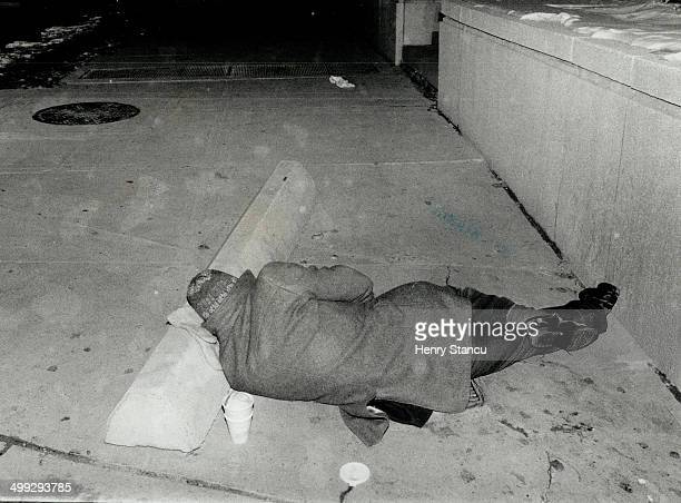 A homeless man uses a mitten atop a concrete barrier for a pillow as he sleeps in freezing temperatures in the Dundas St W Simcoe St area last night...