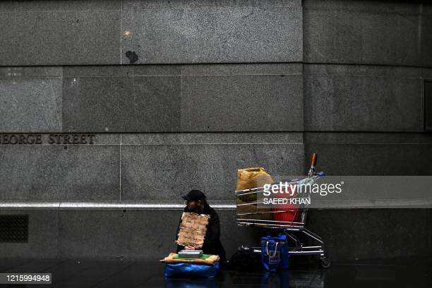 Homeless man waits for charity in the rain in central Sydney on May 29, 2020. - The government has been keen to reopen the economy after a...