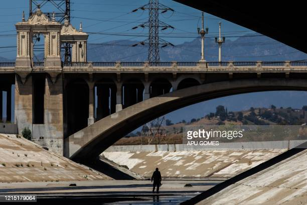 A homeless man walks along the concrete banks of the Los Angeles River during the novel Coronavirus COVID19 pandemic in Los Angeles California on May...